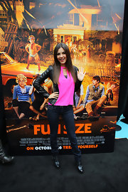 Victoria Justice kept it casual, pairing black buckled booties with her jeans, hot pink top, and leather jacket.