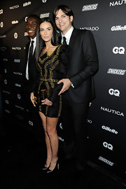 Demi Moore posed with Ashton in a black strong-shouldered cocktail dress with gold embroidery at the GQ's Gentlemen's Ball.
