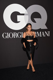 Christina Milian showed off her enviable figure in a strappy black crop-top by Misha Collection during the GQ and Giorgio Armani Grammy after-party.