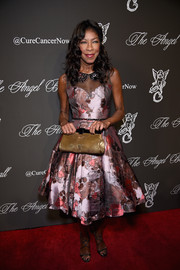 Natalie Cole complemented her dress with a chic gold frame clutch.