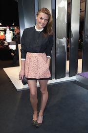 Sophia dons a tweed mini skirt with a modest blouse for this stunning Fashion Week ensemble.