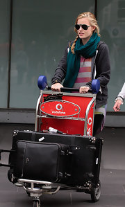 Georgia wears a long green pashmina scarf as she pushes her luggage from the airport.