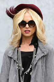 The Stylish Rachel Zoe made quite the appearance at the Giorgio Armani Fashion Show while wearing a burgundy dress hat with a feather embellishment.