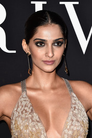 Sonam Kapoor slicked her hair back into an elegant center-parted chignon for the Giorgio Armani Prive show.