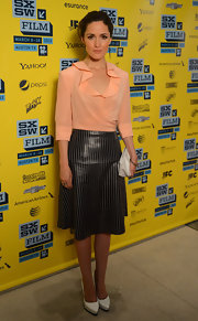 Rose Byrne paired a soft peach blouse with ruffles with a sleek black skirt for an unexpected mix of textures.