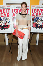 For a splash of color to her neutral outfit, Hilary Rhoda accessorized with an oversized red-orange foldover clutch.