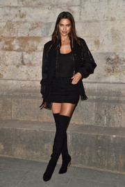 Irina Shayk looked saucy in a black denim mini skirt and a semi-sheeer top at the Givenchy fashion show.
