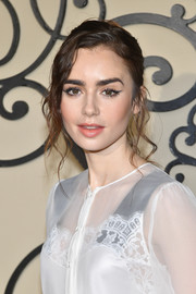 Lily Collins wore her hair in a messy-glam updo at the Givenchy Spring 2018 show.