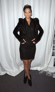 Rihanna's black, strappy ankle boots are suede and have a pointed toe. This style perfectly pairs with a mini for fall.