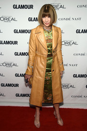 Anna Wintour posed on the Glamour Women of the Year red carpet wearing a chic mustard leather coat over a silk dress.
