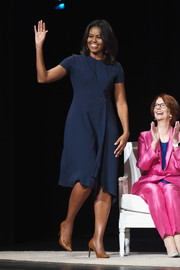"Michelle Obama wore a short-sleeved navy day dress with tan pumps for the Glamour ""Power of an Educated Girl"" panel."
