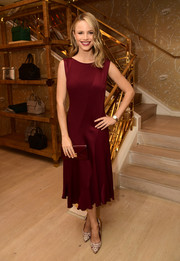 Halston Sage polished off her look with a burgundy envelope clutch.