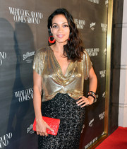 Rosario Dawson accessorized with a textured red leather clutch at the What Goes Around Comes Around one-year anniversary party.