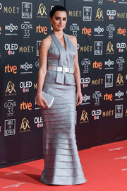 Penelope Cruz complemented her dress with a silver satin clutch.