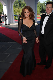 Raquel Welch arrived at the grand opening of Casino Club wearing a stunning black mermaid gown with sheer sleeves.