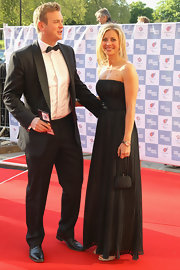 Holly Branson attended the Greatest Team Rises BOA Olympic concert wearing an elegant long black gown with tiny pleats.