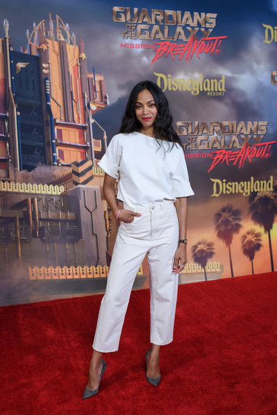 Zoe Saldana was casual-chic in a loose white blouse at the Guardians of the Galaxy - Mission: Breakout! grand opening.