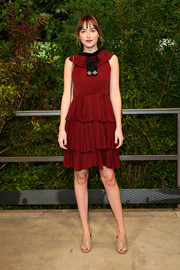 Dakota Johnson went for ultra-feminine flair in a tiered red cocktail dress by Gucci during the label's fashion show.