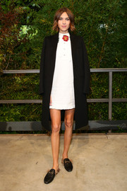 Alexa Chung arrived for the Gucci fashion show wearing a black boyfriend coat over a little white dress.