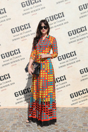 Dakota Johnson brought a vibrant burst of color to the Gucci fashion show with this printed maxi shirtdress from the label.