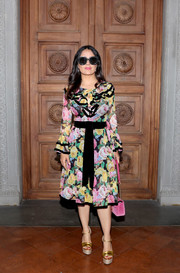 Salma Hayek looked festive in a Gucci floral ruffle dress during the label's Cruise 2018 show.