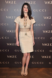 Gemma wears an ecru coctkail dress with a unique lace up necklin for the Gucci Rue Royale Reopening party.