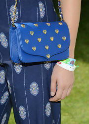 Sophia Bush paired this electric blue shoulder bag that featured a gold chain strap and gold heart embellishments for her look at the H&M event at Coachella.