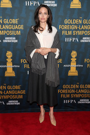 Angelina Jolie kept it simple and classic in a black Falconeri midi skirt paired with a white button-down at the Golden Globe Foreign-Language Film Symposium.