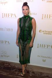 Eva Longoria complemented her dress with a pair of bejeweled green sandals by Olgana Paris.