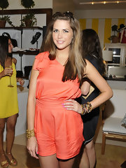 Erin jumps for style in a salmon silk romper for the Hamptons Magazine event.