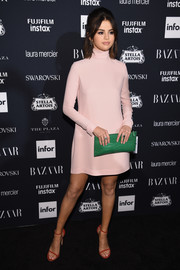 Selena Gomez added an extra pop of color with a green croc-embossed clutch by Coach.