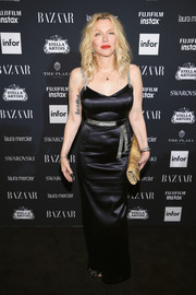 Courtney Love oozed sultry elegance in a form-fitting black satin gown with a bedazzled waistband and shoulder straps at the Harper's Bazaar Icons event.