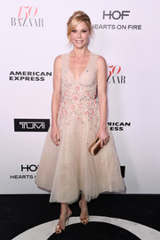 A gold satin clutch polished off Julie Bowen's chic ensemble.