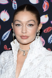 Gigi Hadid styled her hair into a sleek center-parted bun for the Harper's Bazaar exhibition.