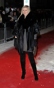 Amanda Wakeley pared down a dramatic coat with sleek black knee high boots. She donned the suede boots over black skinnies.