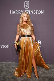 Paris Hilton went for high shine in a gold halter gown with a thigh-high slit at the amfAR New York Gala.