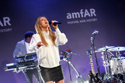 Ellie Goulding performed at the amfAR New York Gala wearing a loose white blouse and a black leather mini.