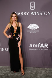 Heidi Klum attended the amfAR New York Gala wearing a black Versace gown adorned with colorful, swirly embroidery.