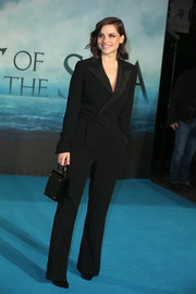 Charlotte Riley complemented her jumpsuit with a classic black leather purse.