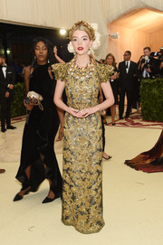 Anya Taylor-Joy kept it classy in an embroidered gold column dress by Dolce & Gabbana Alta Moda at the 2018 Met Gala.