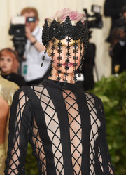 Cara Delevingne looked avant-garde wearing this black headdress by Marianna Harutunian at the 2018 Met Gala.