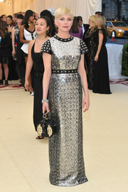 Michelle Williams looked fierce at the 2018 Met Gala in a silver sequined Louis Vuitton gown with a studded neckline, sleeves, and waist.