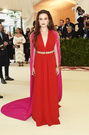 Katherine Langford was a vision in a red Prada gown with a flowing fuchsia cape at the 2018 Met Gala.