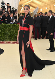 Taylor Hill styled her dress with red satin ankle-tie pumps by Christian Louboutin.