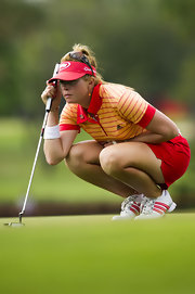 Paula Creamer wears a red sun visor, promoting her sponsors.