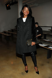 Genevieve Jones looked edgy carrying a black leather clutch with gold studs at the Hood By Air fall 2013 fashion show.