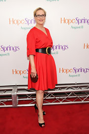Meryl's small brown clutch added sophisticated panache to her bright red dress.