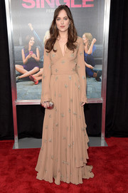 Dakota Johnson paired her lovely gown with a gold clamshell clutch.