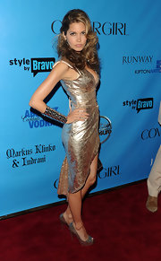 Indrani wore a dangerous-looking spiked arm cuff with a metallic evening dress and peep toe pumps.