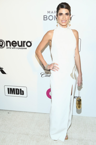 Nikki Reed styled her dress with a gold pill wristlet by Marzook.